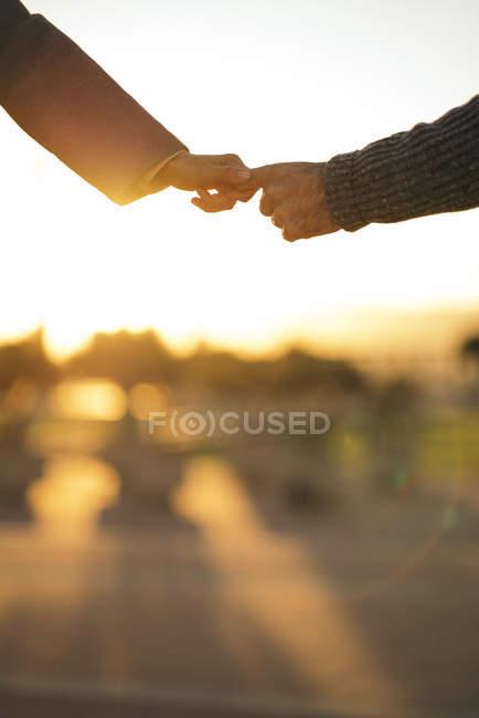 Крупным планом влюбленная пара, держащаяся за руки на закате — стоковое фото