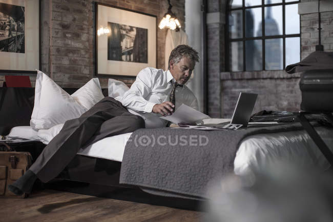Man using laptop in hotel room — Stock Photo