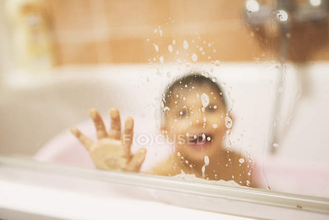 Toddler behind glass pane in bath tub — Stock Photo