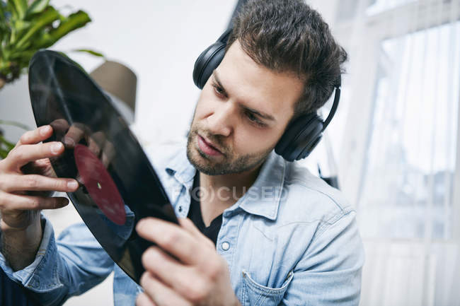 Young man wearing headphones holding record — Stock Photo