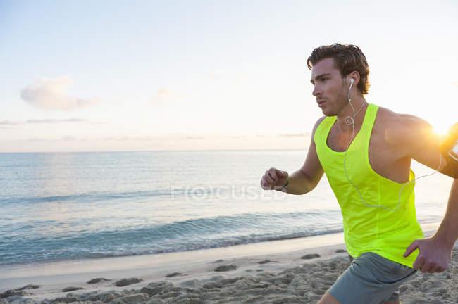 Corredor com fones de ouvido na praia de manhã — Fotografia de Stock