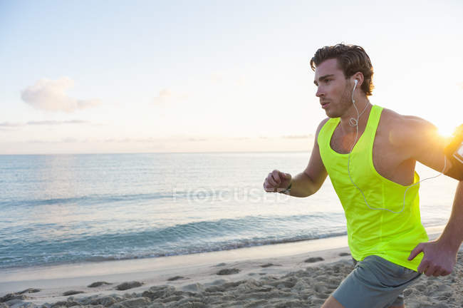 Jogger with earphones at beach in morning — Stock Photo