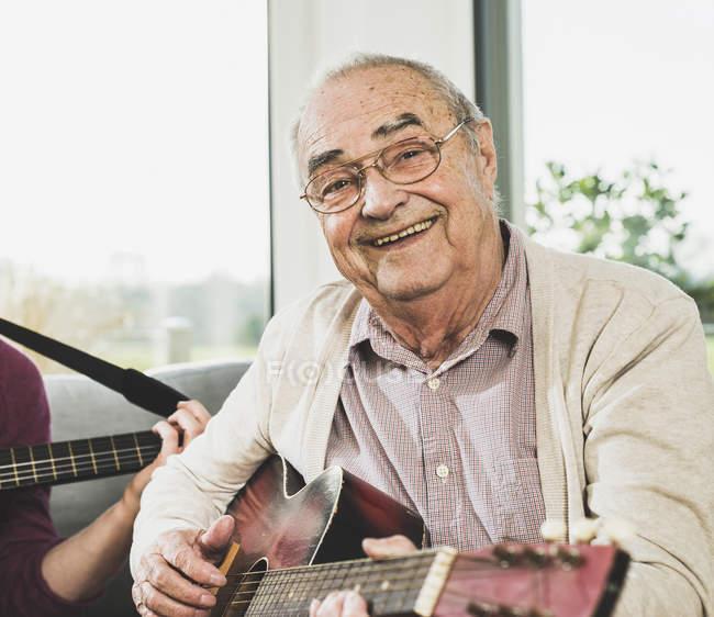 Portrait d'un homme senior, jouer de la guitare à l'intérieur, — Photo de stock