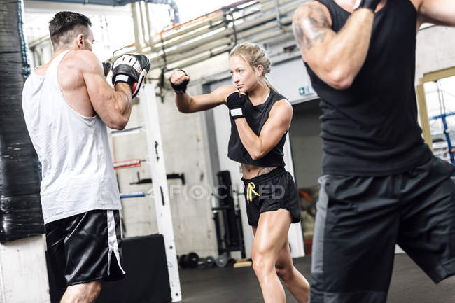 Kaukasische Boxerin sparring mit Trainer — Stockfoto
