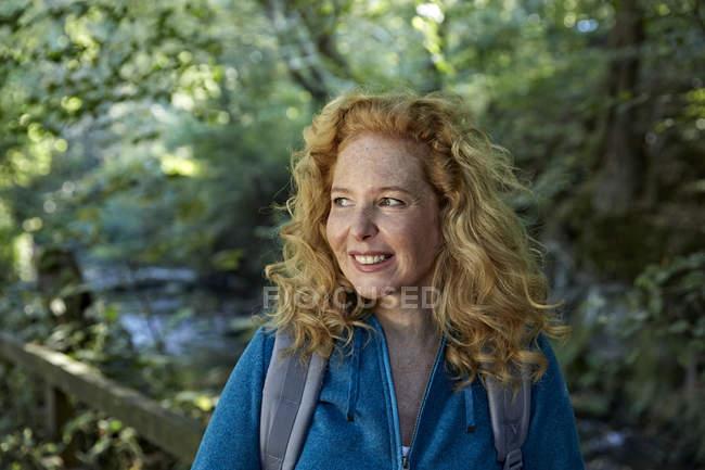 Портрет улыбающейся женщины, путешествующей по лесу — стоковое фото