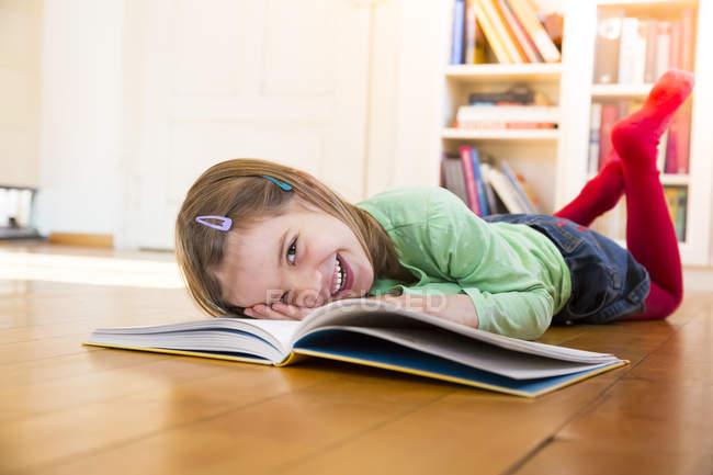 Rire petite fille couchée sur le sol avec un livre — Photo de stock