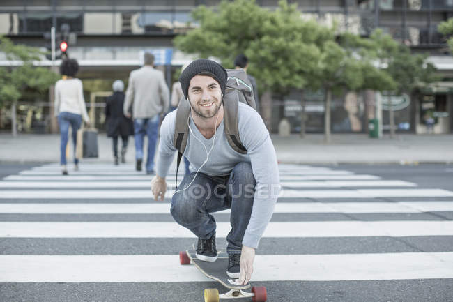 Young man skateboarding on zebra crossing — Stock Photo