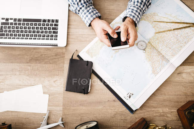 Man sitting at his desk with smartphone, laptop and map planning trip — Stock Photo