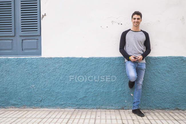 Joven sonriente apoyado contra una pared - foto de stock