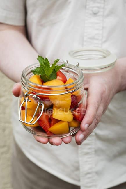 Pessoa, segurando o frasco com salada de frutas — Fotografia de Stock
