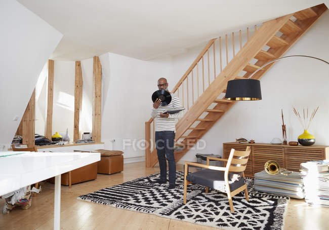 Man standing in his living room holding record — Stock Photo