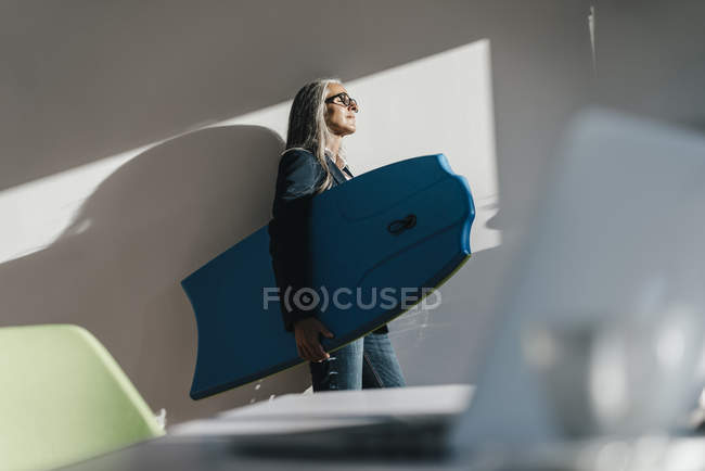 Businesswoman holding surfboard in office and enjoying sunlight — Stock Photo
