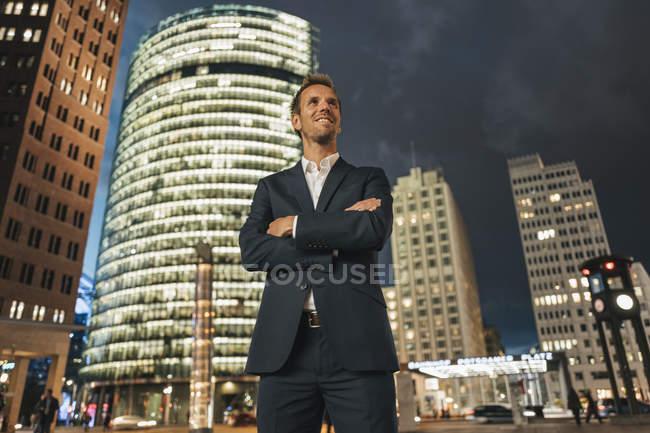 Allemagne, Berlin, homme d'affaires souriant debout devant Potsdamer Platz la nuit — Photo de stock