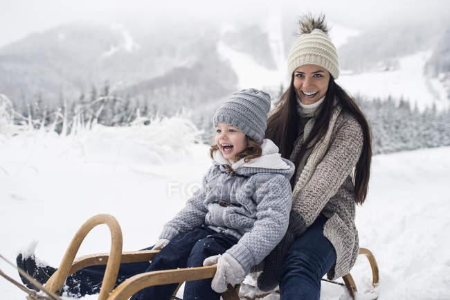 Счастливая мать с дочерью на санях в зимнем пейзаже — стоковое фото