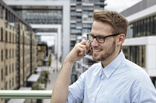 Smiling young man on cell phone outdoors — Stock Photo