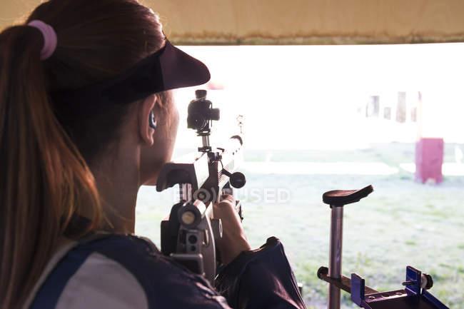 Mulher com um rifle esportivo em um campo de tiro — Fotografia de Stock