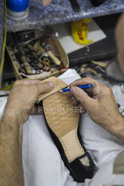 Sapateiro marcando a sola de um sapato com um lápis — Fotografia de Stock