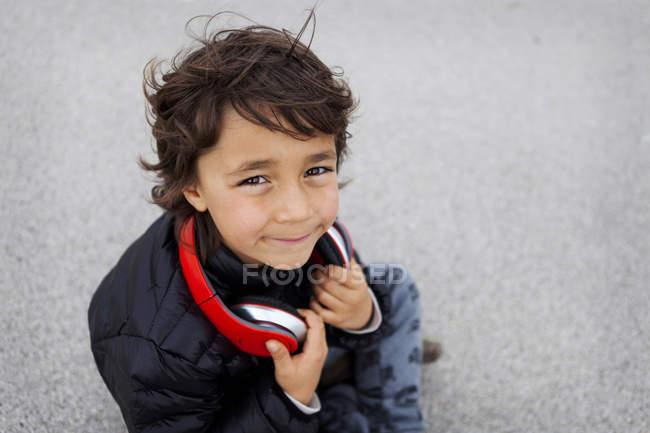 Портрет мальчика с наушниками, смотрящего в камеру — стоковое фото