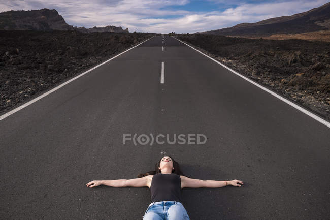 Spain, Tenerife, woman lying on an empty road with outstretched arms — Stock Photo