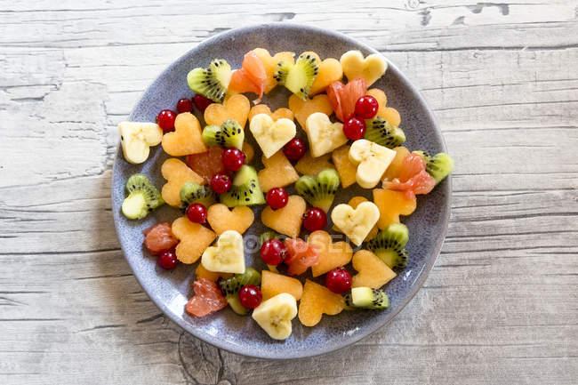 Vista superior de la placa con diferentes trozos de fruta en forma de corazón - foto de stock