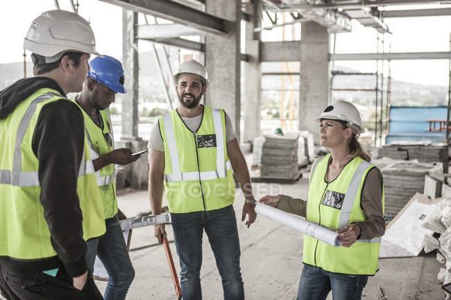 Woman in protective workwear and construction workers in construction site — Stock Photo