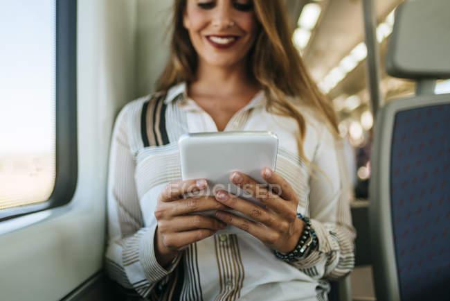 Усміхається жінка в поїзді за допомогою планшета — стокове фото