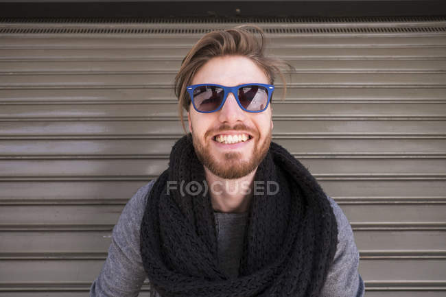 Portrait of grinning man with blue sunglasses in front of roller shutter — Stock Photo