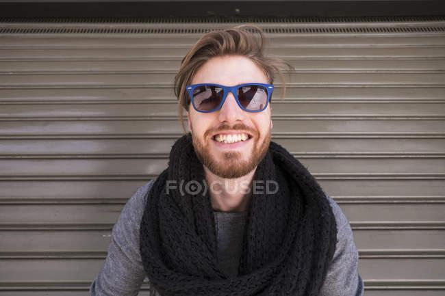 Retrato de homem sorridente com óculos azuis na frente do obturador — Fotografia de Stock