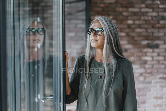 Woman with long grey hair reflected in window in office — Stock Photo