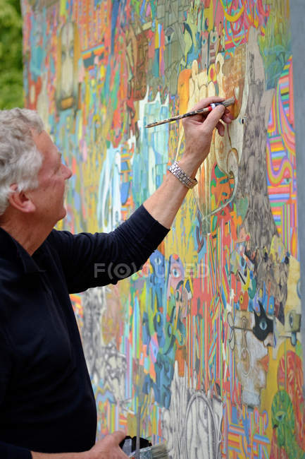 Side view of senior male painter at work — Stock Photo