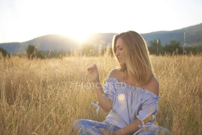 Blond woman sitting on meadow at backlight — Stock Photo