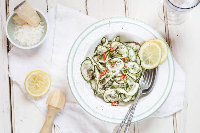 Салат из огуречной тальятелли с острым лимонным соусом и пармезаном — стоковое фото