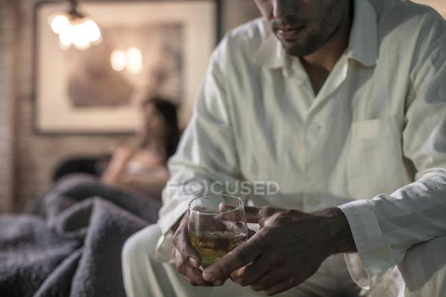 Homem sentado na cama com bebida forte — Fotografia de Stock