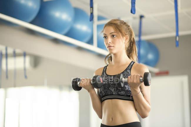 Junge Frau Training Bizeps im Fitness-Studio — Stockfoto