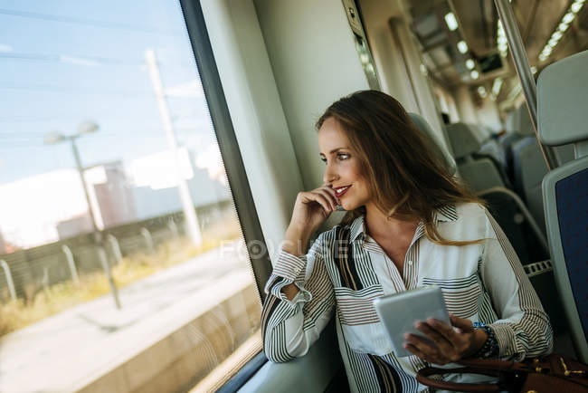 Smiling woman on a train using a tablet — Stock Photo