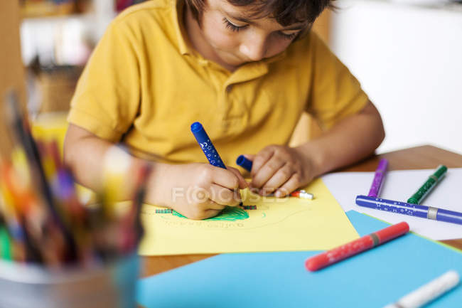 Little boy drawing on yellow paper — Stock Photo