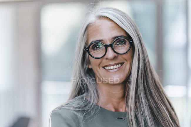 Portrait of smiling woman with long grey hair looking at camera — Stock Photo