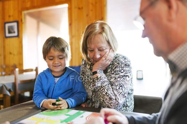 Jugar ludo con el nieto de abuelos - foto de stock