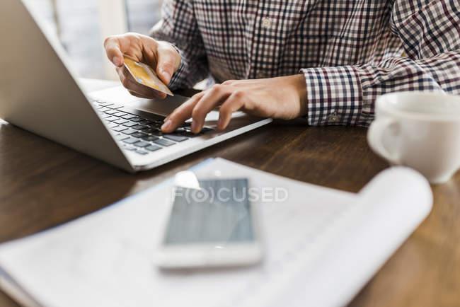 Zugeschnittenes Bild von Mann mit Laptop und Holding-Kreditkarte — Stockfoto