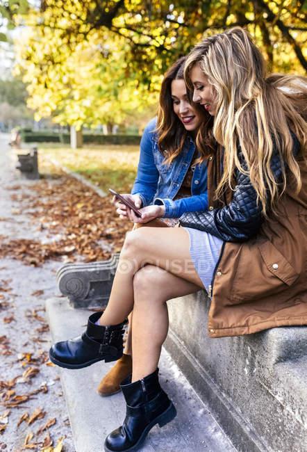 Duas melhores amigas sentadas no banco e usando o smartphone no parque no outono — Fotografia de Stock