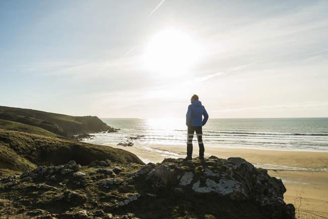 Uomo in piedi sulla roccia sulla costa al tramonto — Foto stock