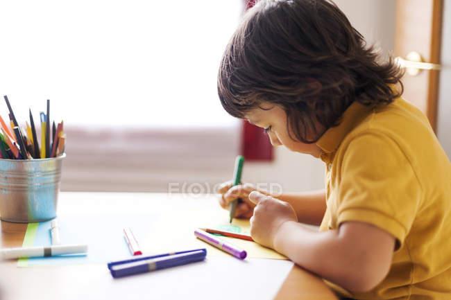 Vista lateral do menino desenho em casa — Fotografia de Stock