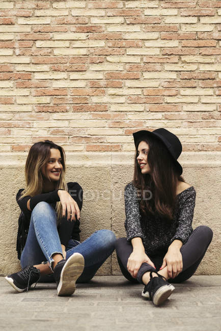 Two best friends sitting in front of facade talking together — Stock Photo