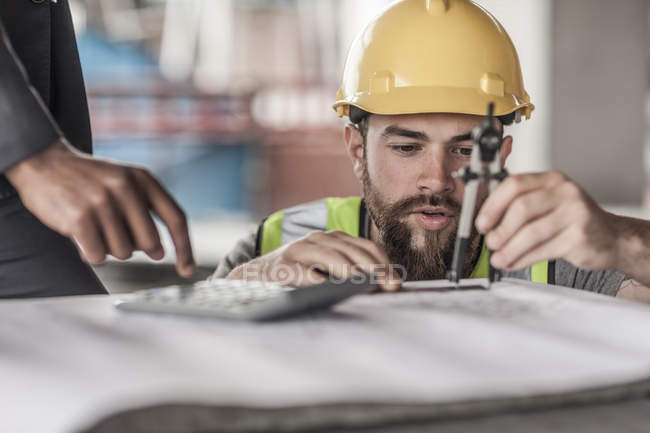 Construction worker and businessman with compasses and calculator — Stock Photo