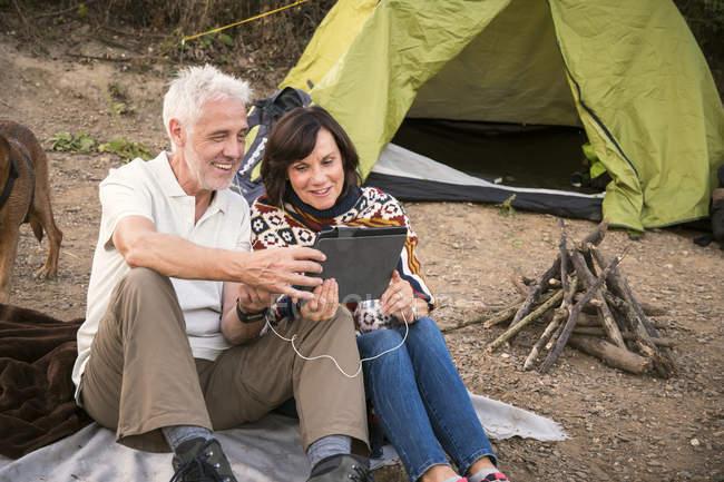 Casal sênior feliz com pastilha em uma tenda — Fotografia de Stock