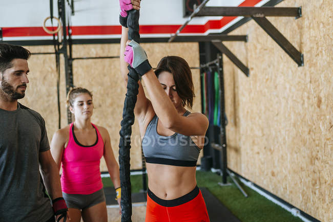 Athlètes regarder femme escalade une corde dans une salle de sport — Photo de stock