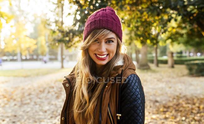 Porträt einer lächelnden jungen Frau mit Wollmütze in einem Park im Herbst — Stockfoto