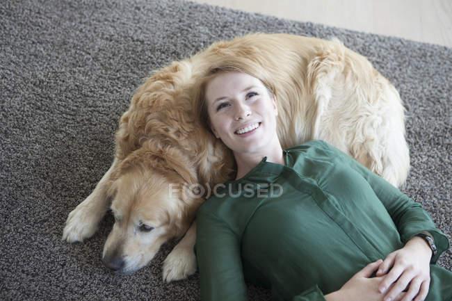 Женщина отдыхает с собакой на ковре — стоковое фото