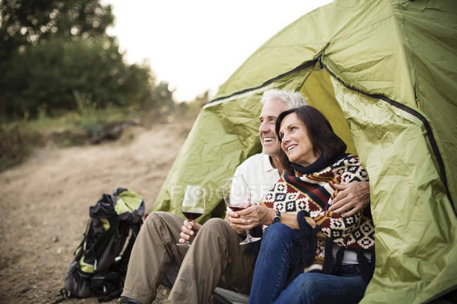 Happy senior couple sitting with wine in a tent — Stock Photo