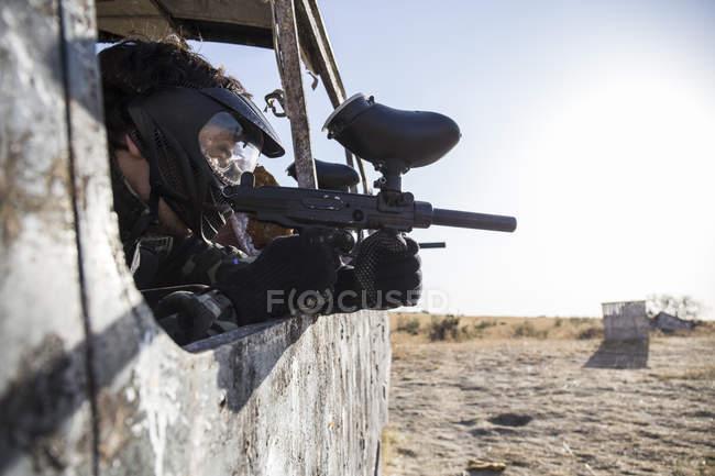 Jogador de paintball barricado em um ônibus de abandonated mirando com a arma de paintball — Fotografia de Stock